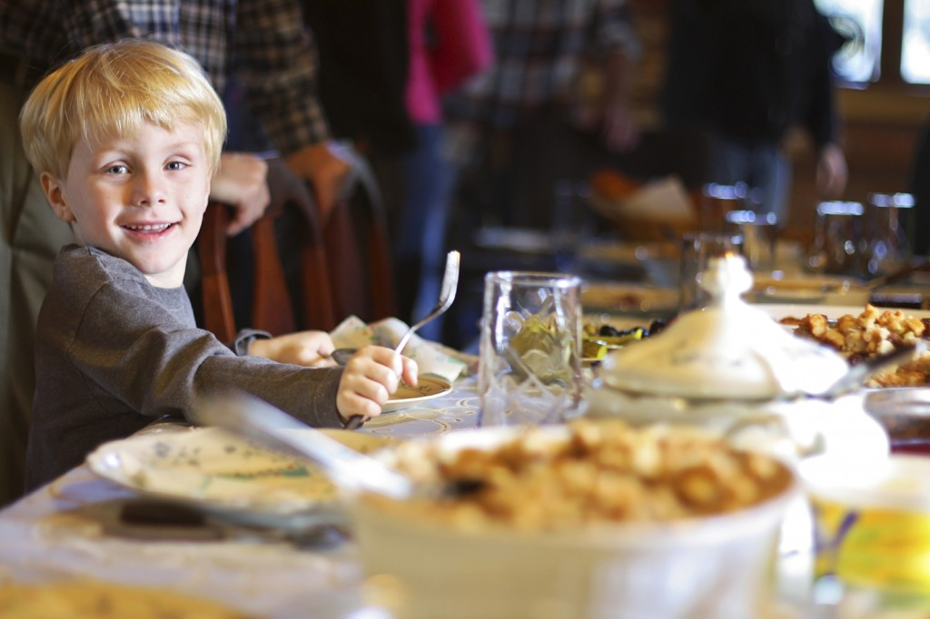 a happy young child is smiling as he sits at the holiday dinner table with a fork and plate, waiting for his meal