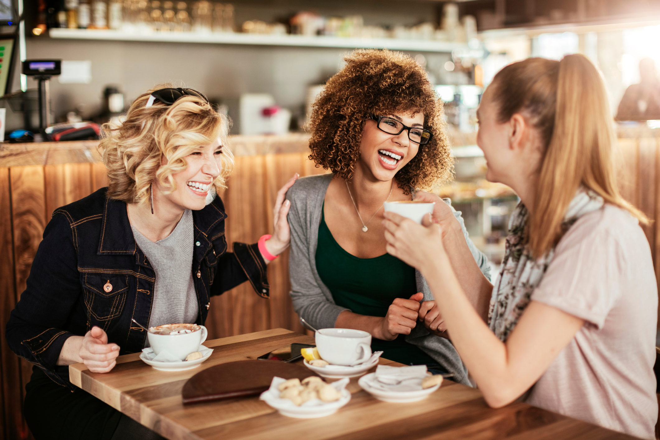 3 young urban professionals laughing it up at a coffee shop
