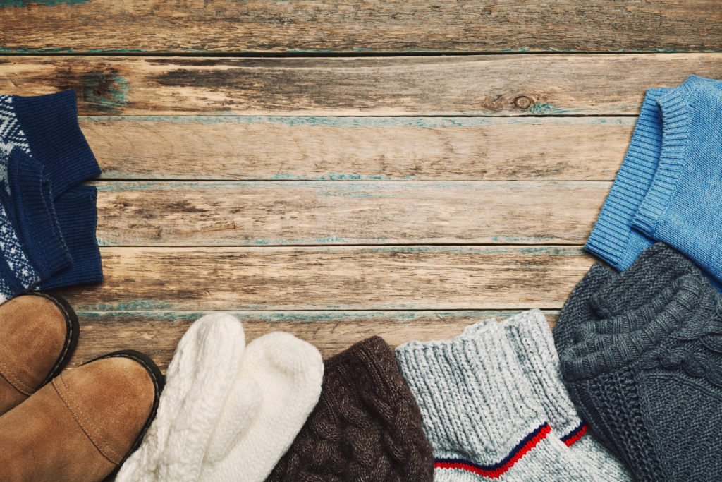 Autumn or winter clothes on wooden vintage background. Flat lay.