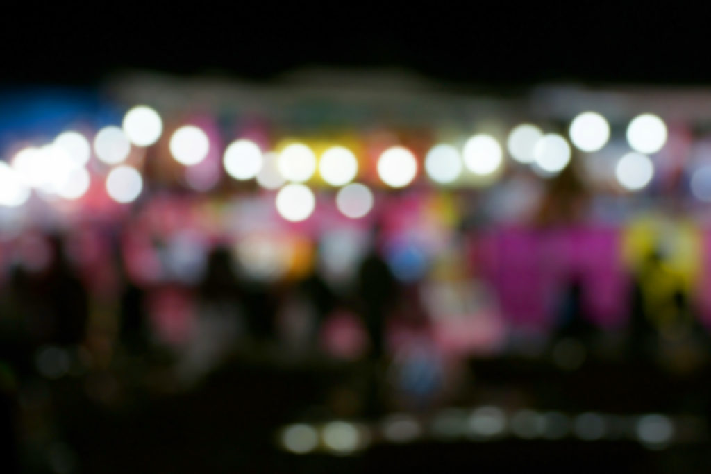 Defocused and blurred image of people at amusement park at night for background usage.