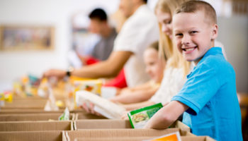 smiling kids working at a food bank