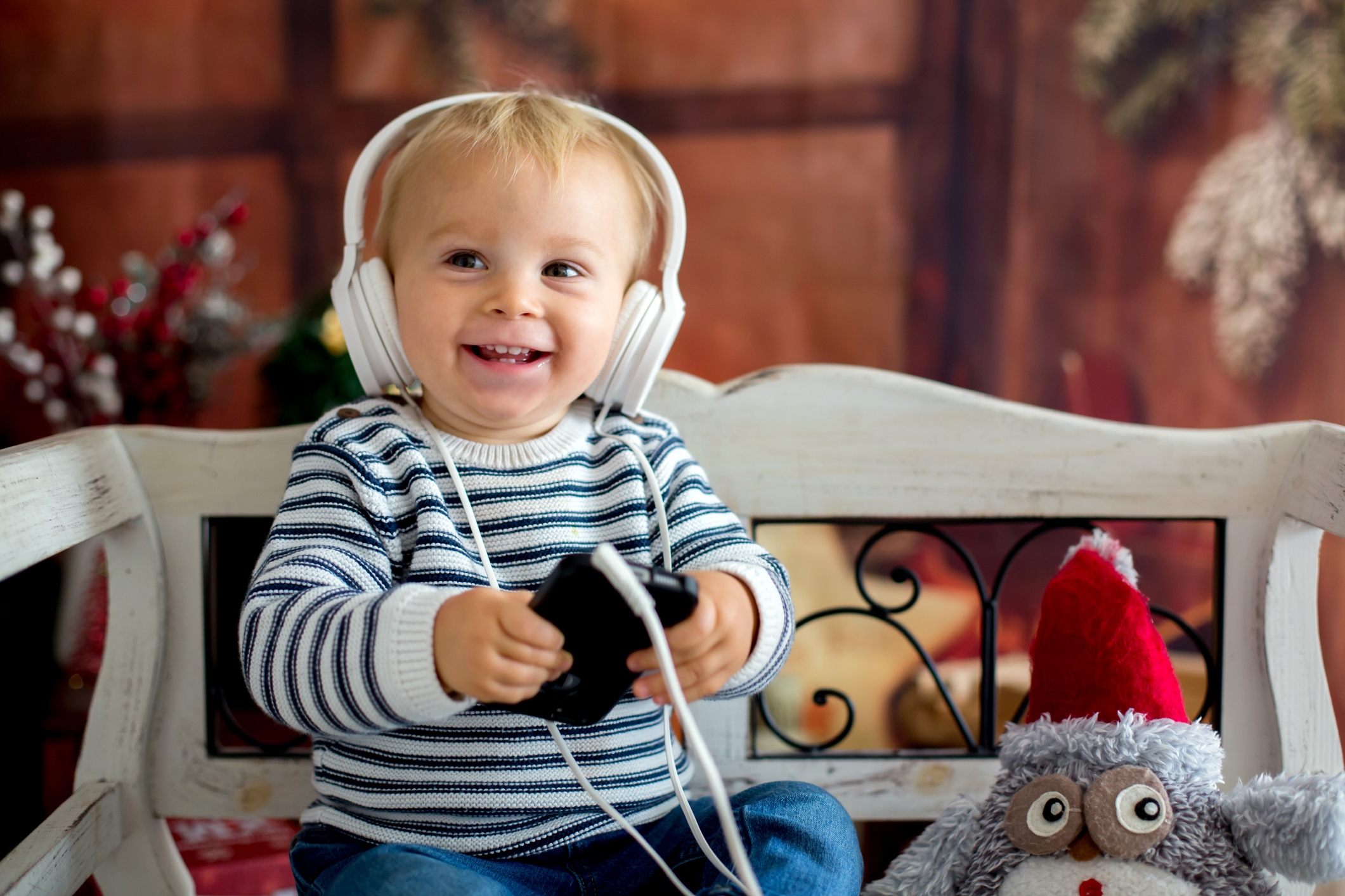 Sweet toddler boy with headphones, listening to music, sitting on rustic bench, christmas decoration behind him