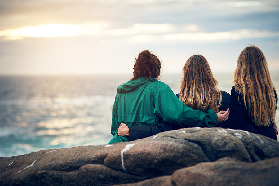 Three women with their arms around each other, watching the sun set over the sea