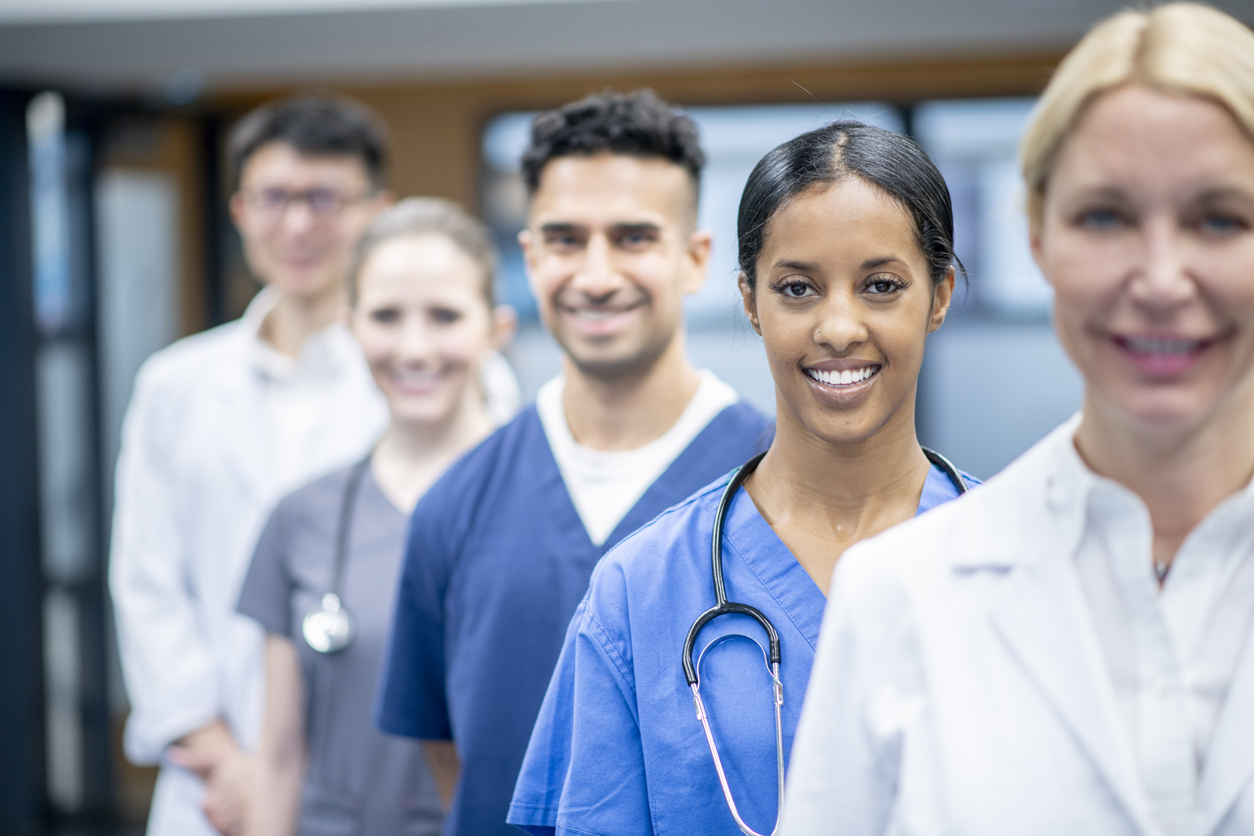 A team of culturally and ethnically diverse medical staff stand in the hallway of a hospital for a team portrait. The men and women are standing in a line and smiling for the photo. Some are wearing blue medical scrubs, others are wearing white lab coats and a few have stethoscopes around their necks.