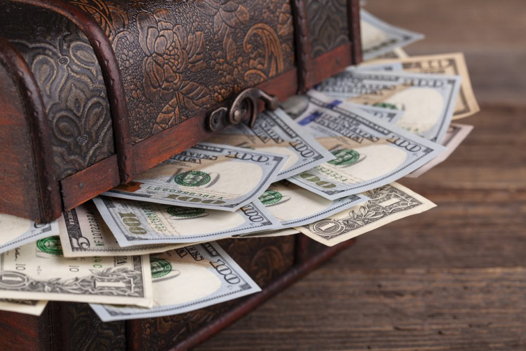 Treasure chest filled with dollars on rustic wooden background